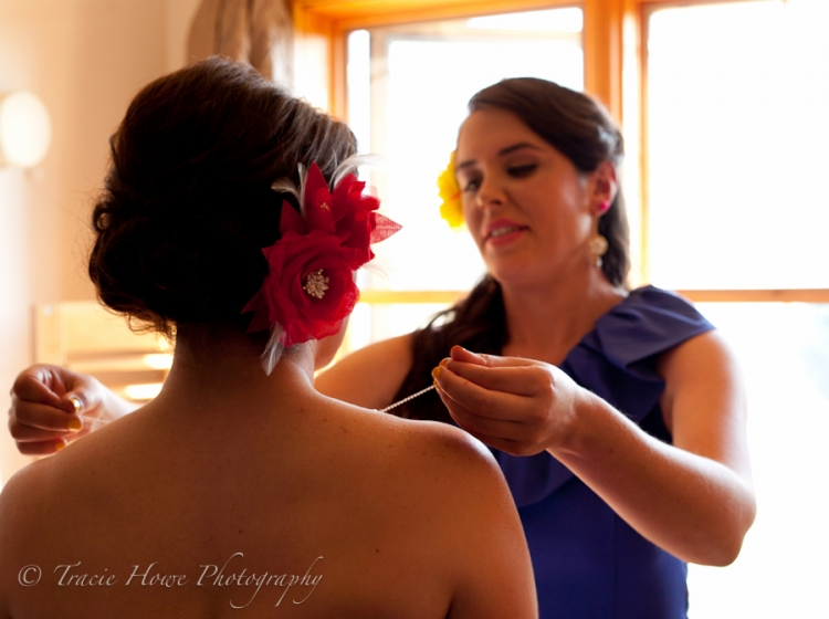 Photo of a sister helping the bride get ready
