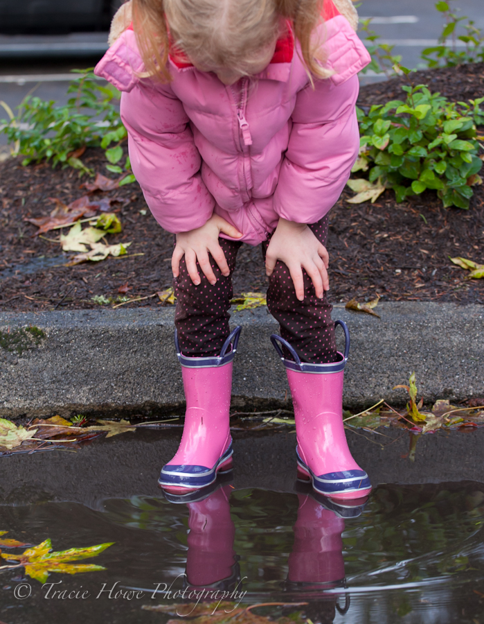 photo of girl looking into puddle