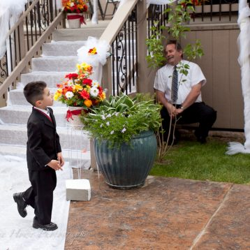 ring bearer playing hide and seek at wedding