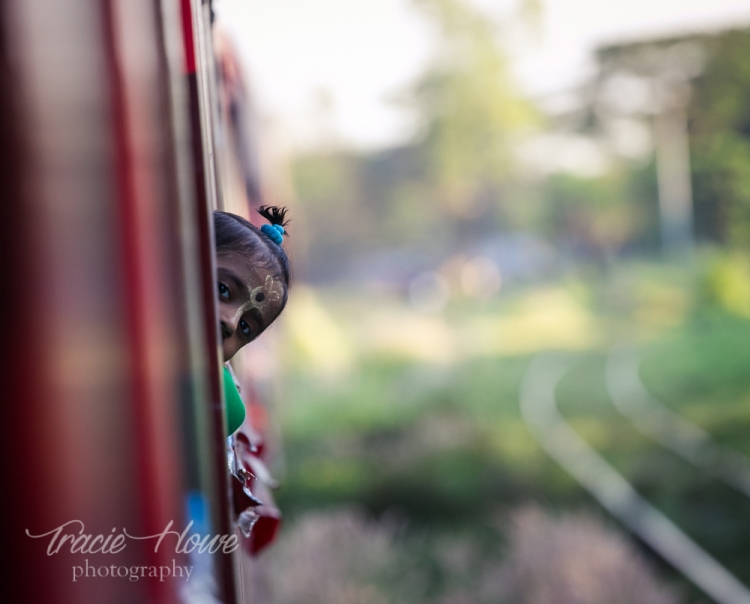 A shy little girl pokes her head out the window on Yangon